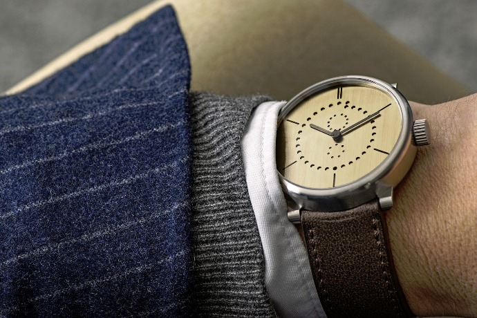 brass watch wearing in the hand