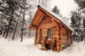 man and dog sits infront of log cabin