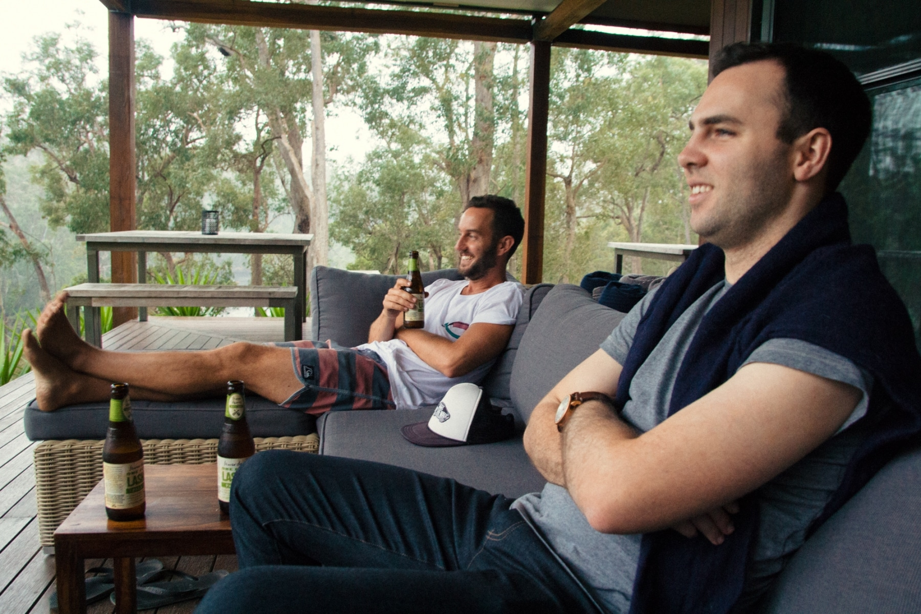 Two men sitting on outdoor sofa