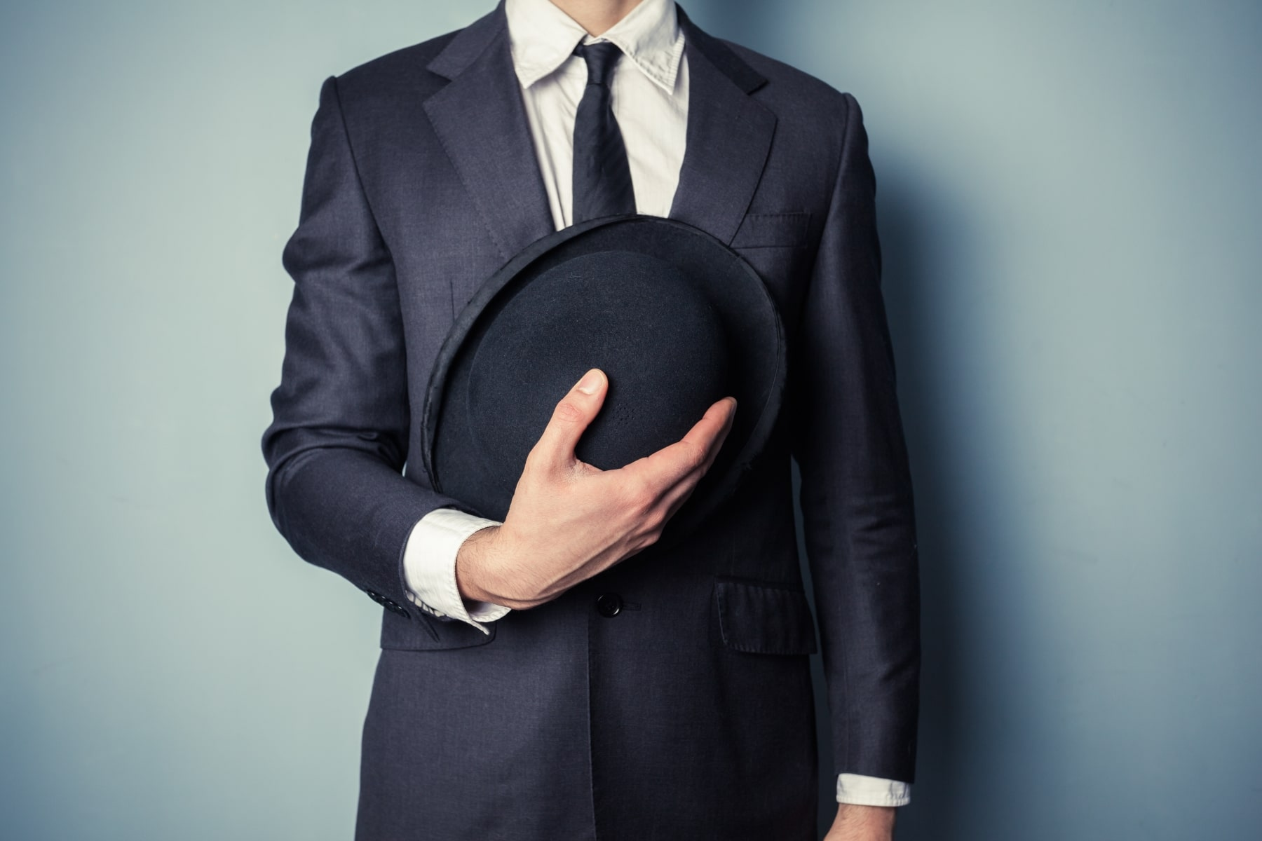 Young man suit holding a bowler hat