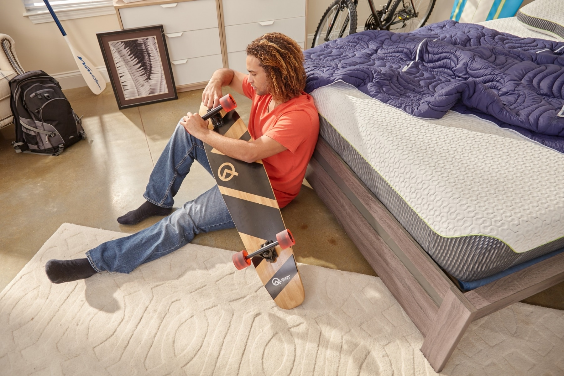 man sitting on floor with skateboard