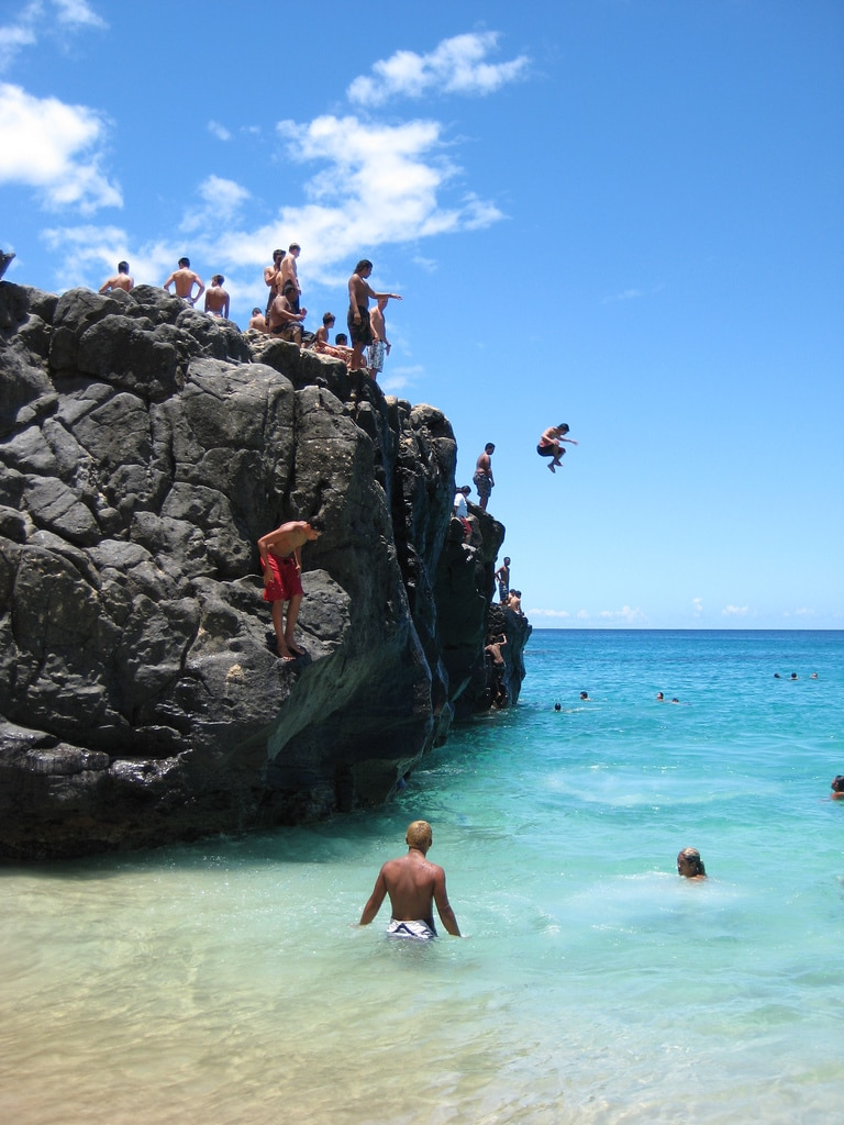 People standing on a cliff and jumping into the ocean