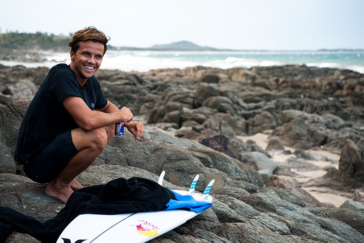 surfer julian wilson sitting on the stone
