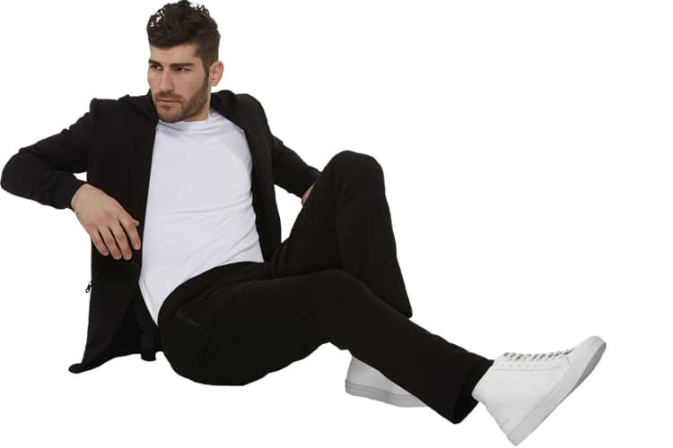 gentleman sitting and wear a black x suit