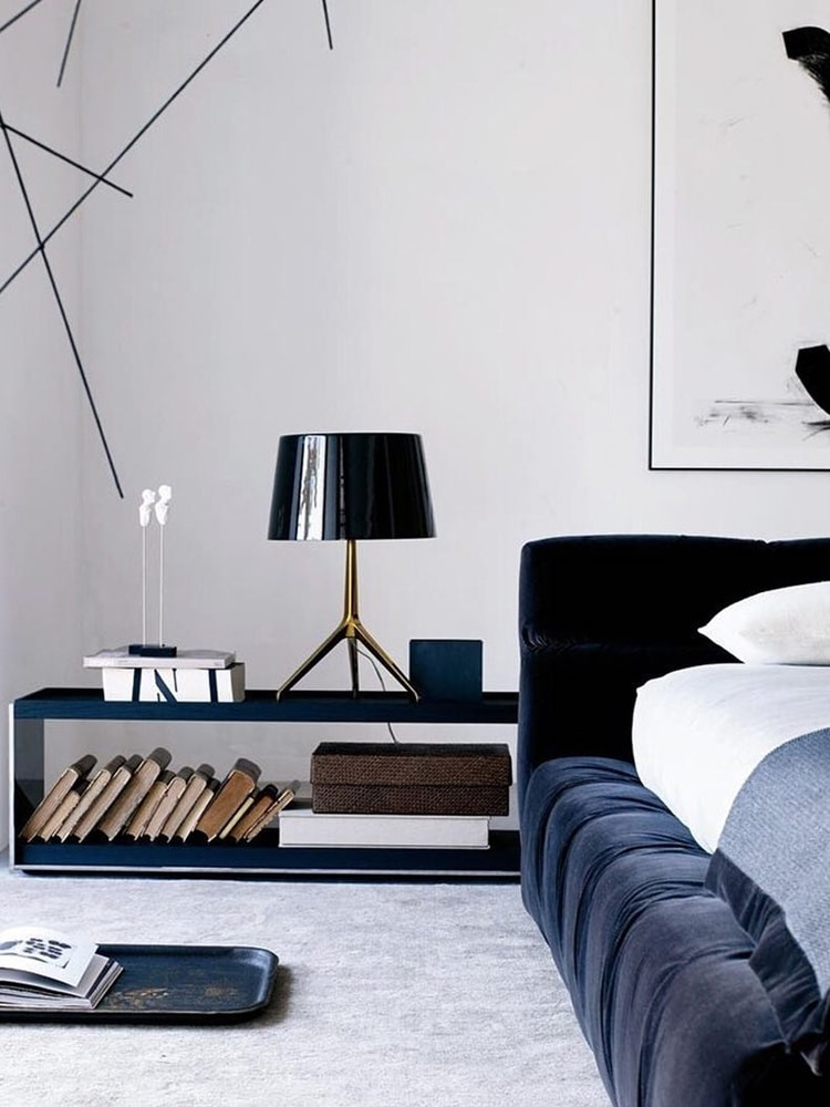 masculine bedroom has a black bed lamp