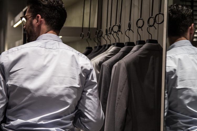 men stand suit showroom