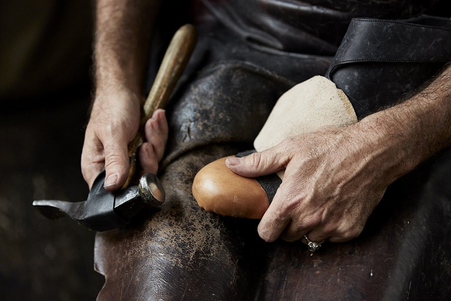 a cobbler repairing the sole of a shoe