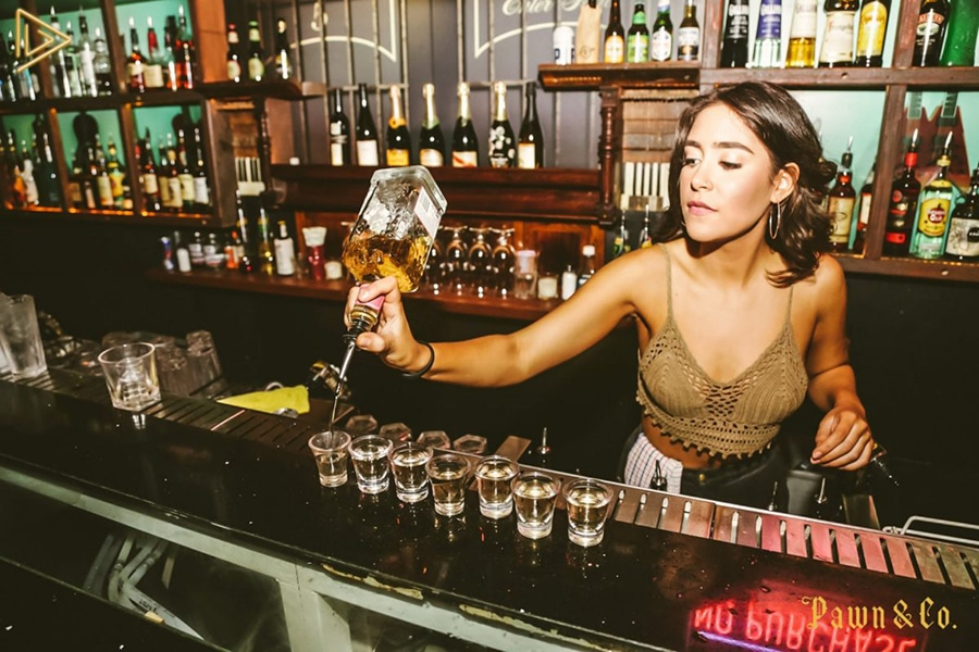 Bartender pouring line of shots