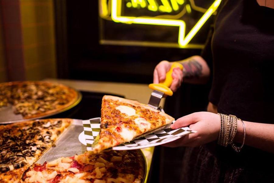 melbourne waiter holding pizza slice