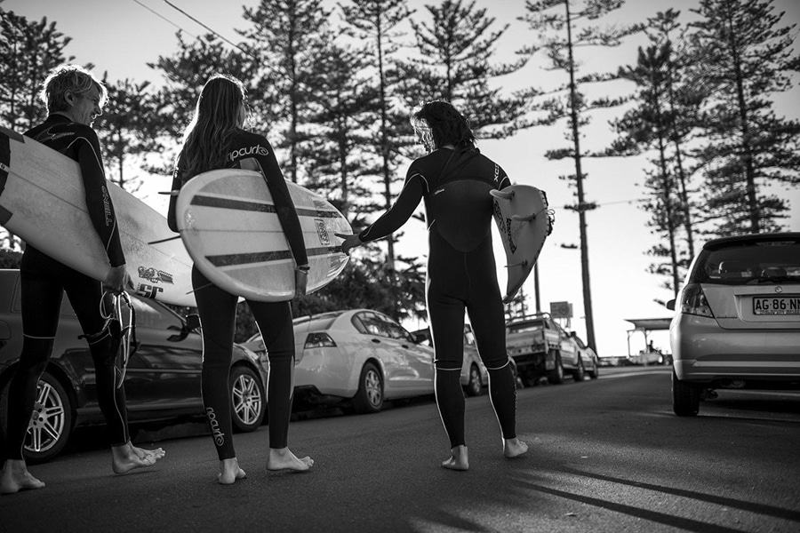 Surfers walk along street with board black and white