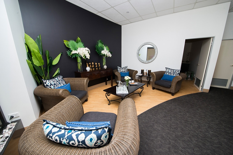 lounge room with plants and arm chairs