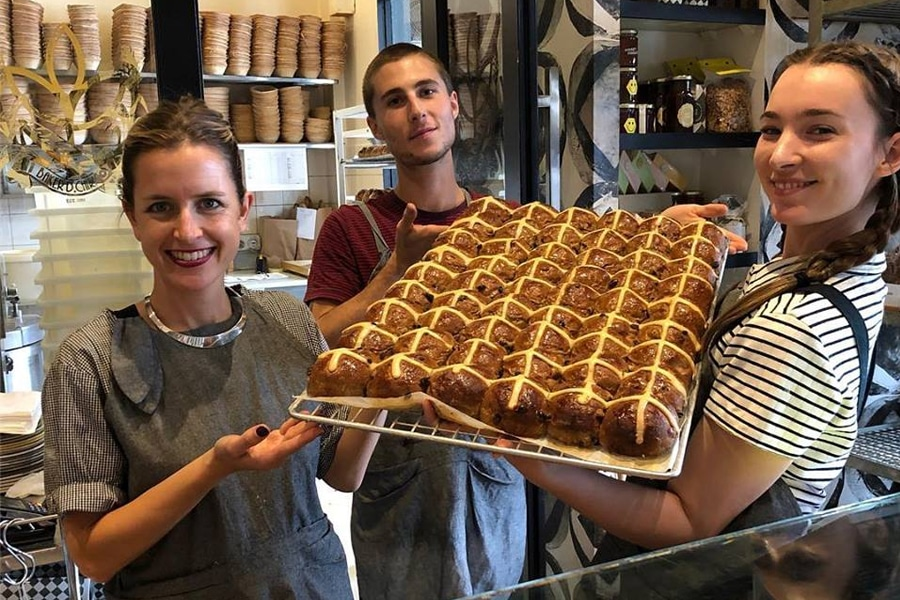baker d chirico workers holding hot cross buns