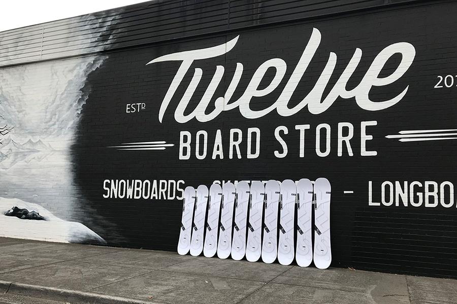 Skate board lined up against Twelve board store mural