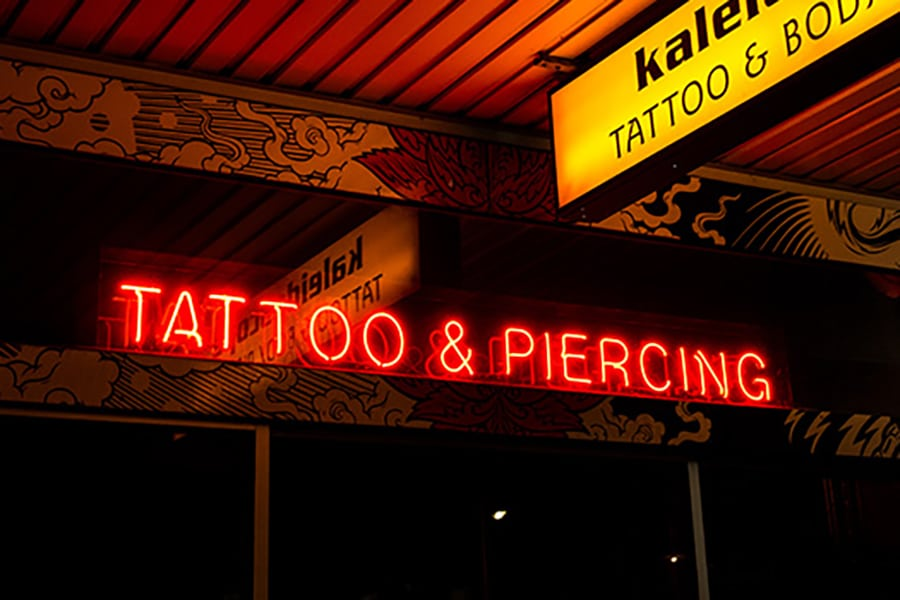 kaleidoscope red neon tattoo and piercing sign