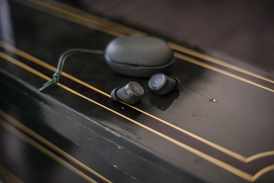 bang and olufsen's beoplay e8 earbuds on table