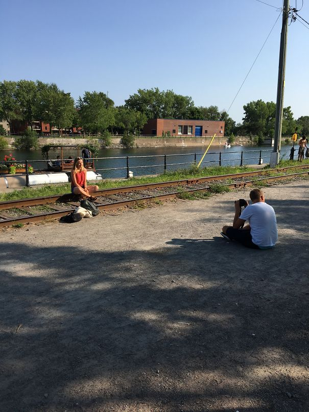 women taking photo to sitting on the rail line