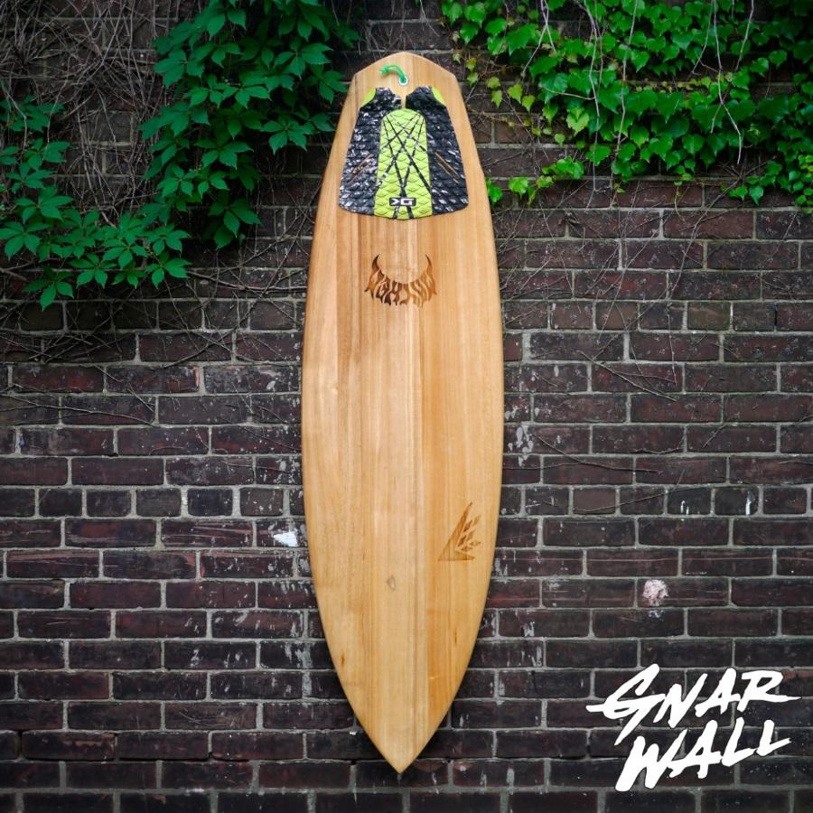 gnarwall surfboard hanging on brick wall