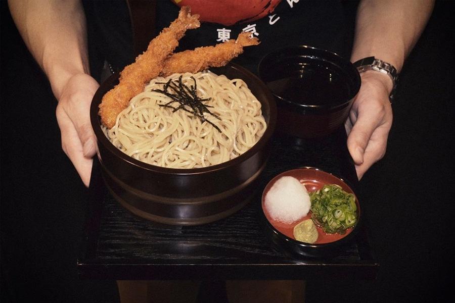 waiter serving shujinko ramen on tray