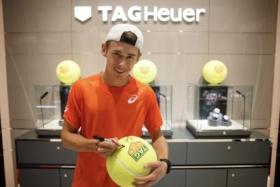 Alex de Minaur signing a big Tennis ball with TAG Heuer logo on it