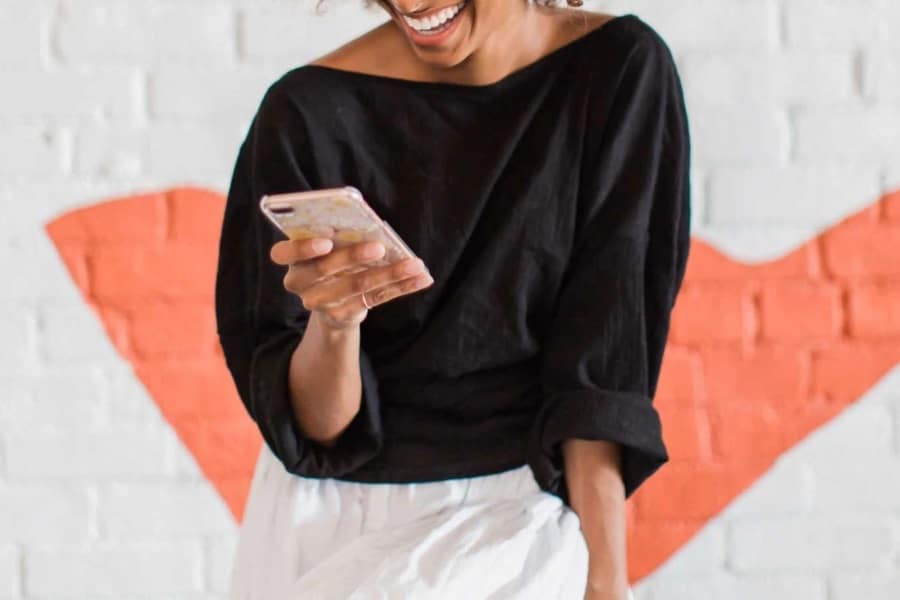 A woman laughing with a phone in her hand