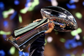 A hand holding Super Bowl trophy