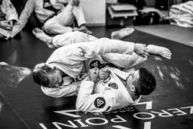 Two men practicing jiu jitsu on floor