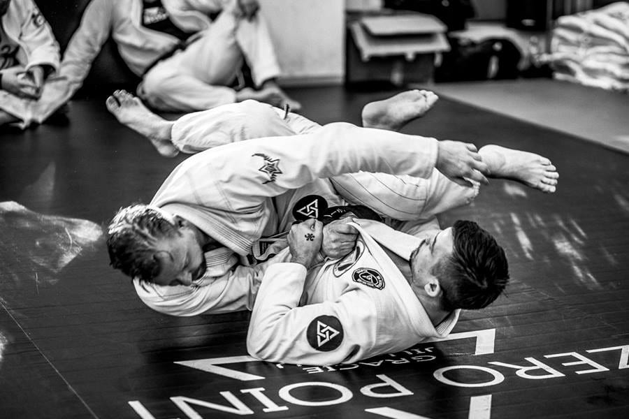 Two men practicing jiu jitsu on floor