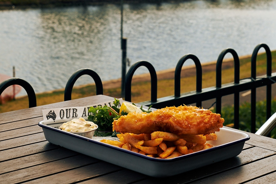 The Boathouse Schnitzel and chips on outdoor table