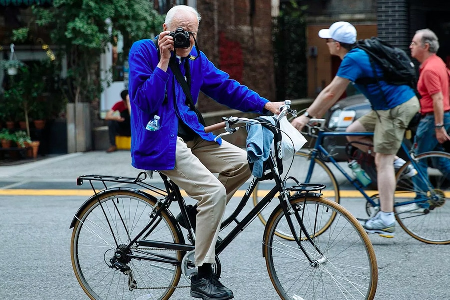 Bill Cunningham in blue jacket on bike