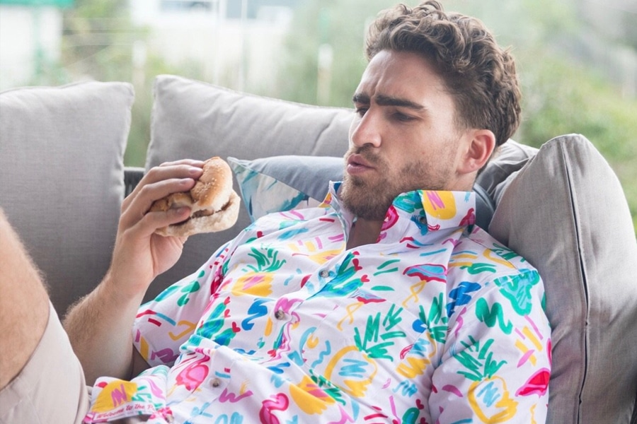 Man in YP thread Hawaiian shirt holding burger