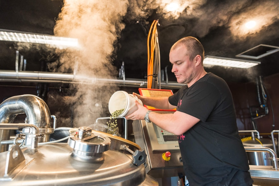brewer pouring ingredient into beer silo