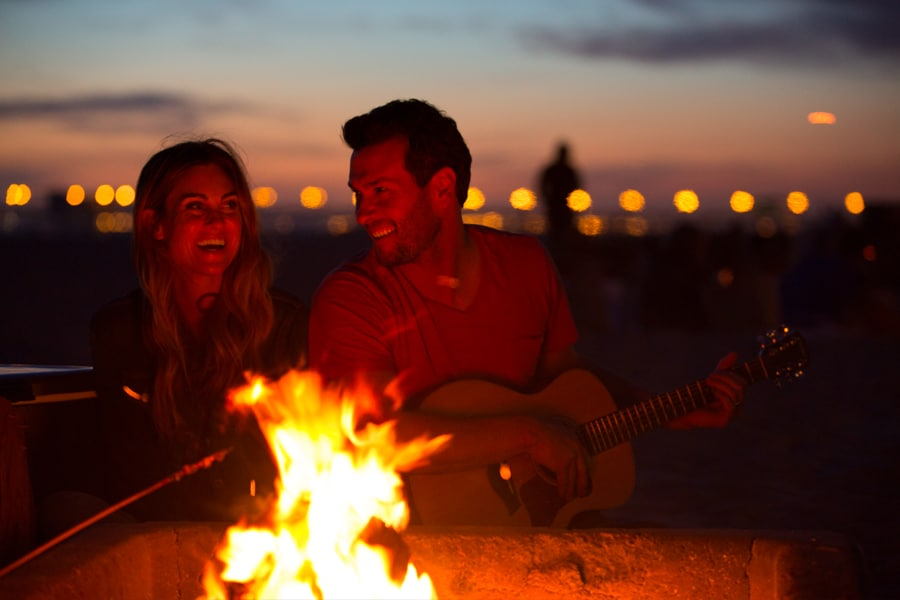 couple at huntington beach bonfire