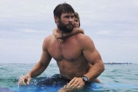 Chris Hemsworth shirtless in water with his child hanging on back