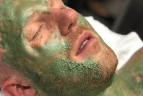 A man's face covered in green facial lotion