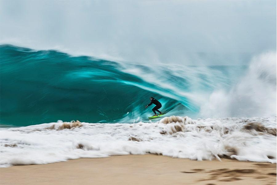 A surfer riding a wave near shore