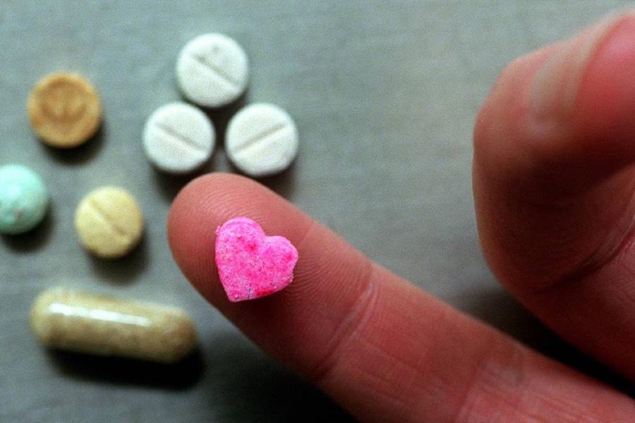 Pink heart pill on finger