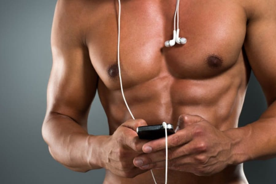 Shirtless man holding a phone with earphones hanging around his neck