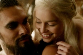 Closeup of Khaleesi with her head on shoulder of Drogo from behind