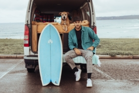 Mitch at the back of van next to his surfboard