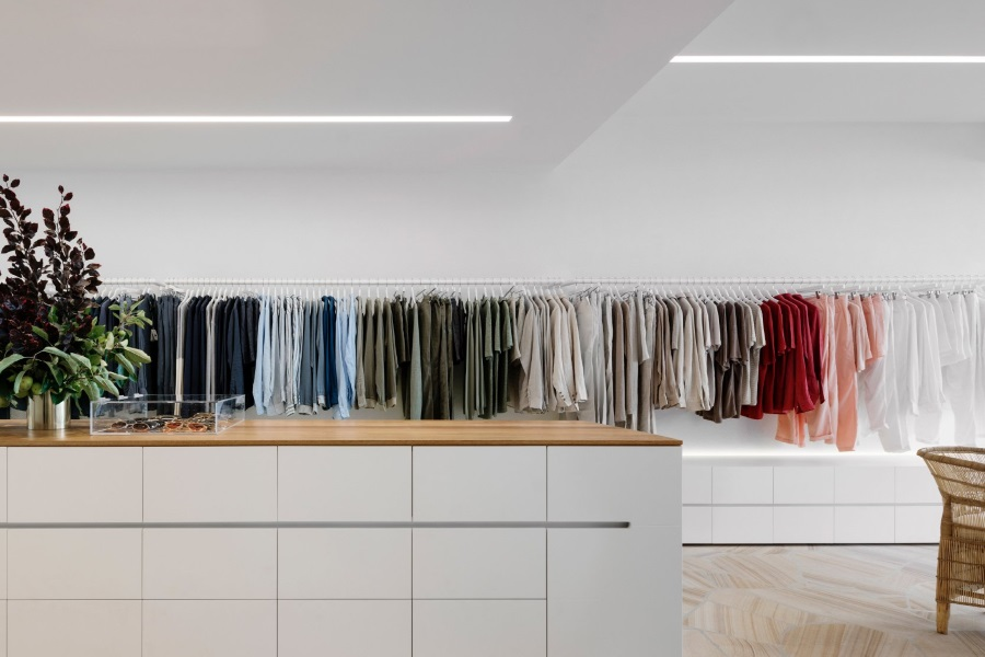 Clothes hanging on racks along a wall