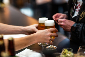 Pair of hands picking glasses of beer from a bar