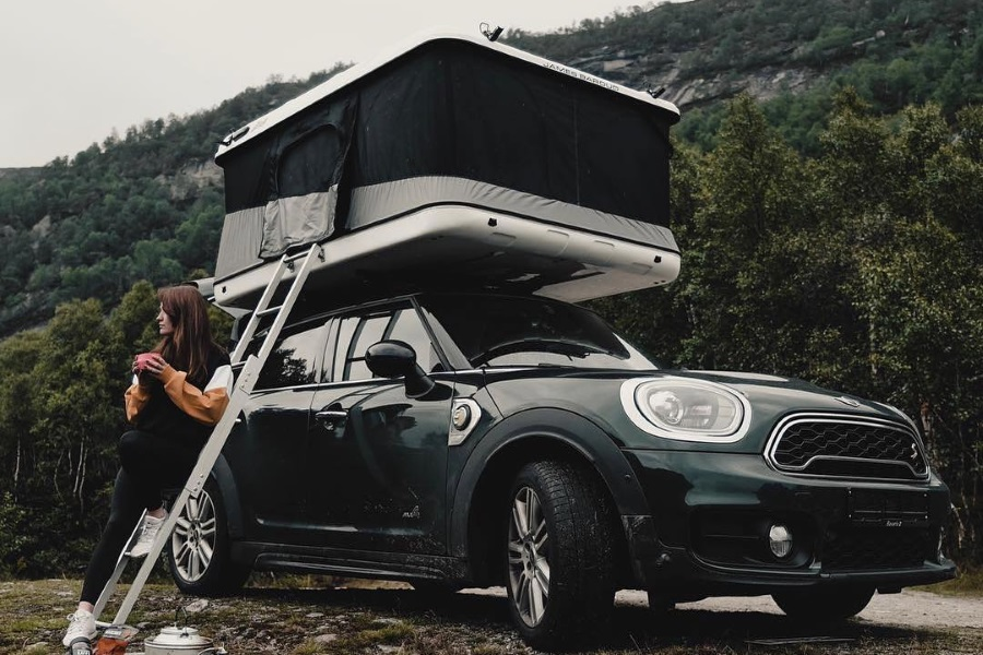 A Mini Cooper three quarter front with a tent on it and a woman sitting on ladder on side