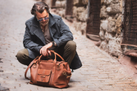 Model sitting withPad and Quill Duffle Briefcase