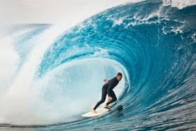 Surfer under a big wave arching over him