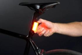 Hand putting Knog Cobber on bar under bike seat