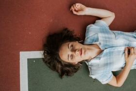 Woman sleeping on a tennis court line