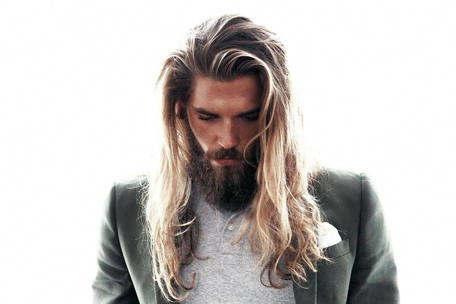 man with long hairstyle looking down