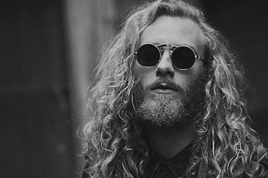 man with long blonde curly hair black and white