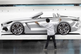 Calvin Luk with his hands on design of side of a car on whiteboard