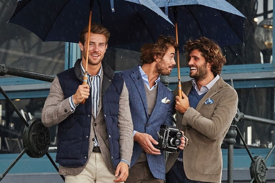 Models in suits and puffer jacketholding umbrellas